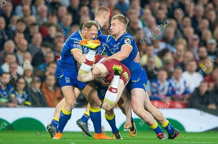 Wigan's Oliver Gildart is tackled by Warrington's Ben Westwood & Mike Cooper.