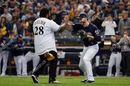Milwaukee Brewers' Ryan Braun (8) greets Prince Fielder as Fielder walks to the mound for the ceremonial first pitch before Game 2 of the National League Championship Series baseball game between the Milwaukee Brewers and the Los Angeles Dodgers, in Milwaukee