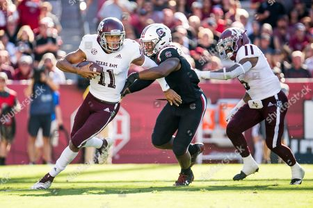 Texas A&M quarterback Kellen Mond (11) runs with the ball against South Carolina defensive lineman Brad Johnson (19) during the first half of an NCAA college football game, in Columbia, S.C