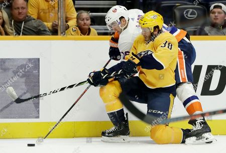 Nashville Predators right wing Ryan Hartman (38) battles New York Islanders left wing Andrew Ladd (16) for the puck in the first period of an NHL hockey game, in Nashville, Tenn