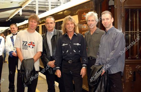 Stock Image of Status Quo Onboard The Orient Express To Launch Their New Album 'heavy Traffic'.l-r John 'rhino'edwards (bass) Francis Rossi (singer) Rick Parfitt (guitar) Andrew Bown (keyboards) And Matt Letley (drummer) Of Status Quo Board The Orient Express At Victoria Station In London Tuesday 30 July 2002. The Band Are Travelling To Portsmouth Where They Will Play An Afternoon Concert On The Hms Ark Royal.