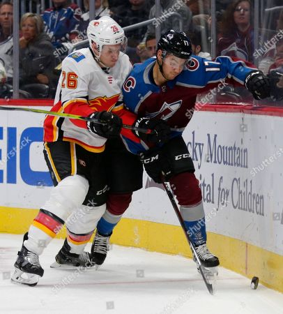 Calgary Flames defenseman Michael Stone (26) challenges Colorado Avalanche center Tyson Jost (17) for the puck during the first period of an NHL hockey game, in Denver