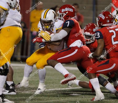 Wyoming running back Nico Evans is bottled up by Fresno State linebacker James Bailey during the second half of an NCAA college football game in Fresno, Calif