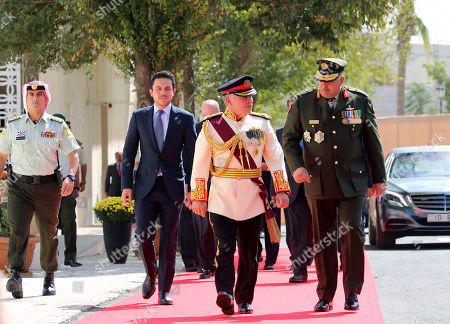 King Abdullah II of Jordan (C) walks with the Crown Prince of Jordan Al Hussein bin Abdullah (2-L) and Chairman of the Joint Chiefs of Staff of the Jordanian Armed Forces Lieutenant General Mahmoud Freihat (R) upon his arrival to give the Throne speech at the inauguration of the 18th parliament's third session, outside the Parliament building in Amman, Jordan, 14 October 2018. The Jordanian king gave his traditional annual throne speech to open the 18th Parliament's third ordinary session to guide the government with a working program for the coming phase.