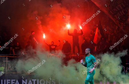 Serbia's goalkeeper Predrag Rajkovic walks on the pitch as Romanian fans light flares during the UEFA Nations League soccer match between Romania and Serbia on the National Arena stadium in Bucharest, Romania