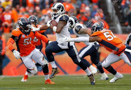 Los Angeles Rams running back Todd Gurley, center, runs as Denver Broncos linebacker Brandon Marshall (54) and linebacker Todd Davis (51) pursue during the first half of an NFL football game, in Denver