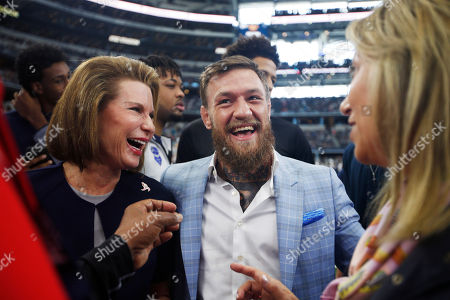 Susan G. Komen for the Cure Founder Nancy Brinker, left, and UFC fighter Conor McGregor are seen on the sidelines before an NFL football game against the Jacksonville Jaguars in Arlington, Texas