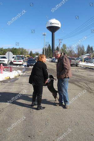 Stock Picture of Heitkamp-Gwinner. In a photo, Democratic Sen. Heidi Heitkamp talks with Richard Murphy and pets Murphy's dog, Burkley, during a campaign stop outside the Bobcat Co. plant in Gwinner, N.D. Heitkamp talked with Murphy and other Bobcat employees during a shift change at the plant, which employs about 1,200 people. Heitkamp is running against Republican Rep. Kevin Carmer in a bid to retain her seat in Congress