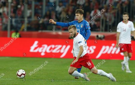 Italy's Nicolo' Barella, right, challenges for the ball with Poland's Jakub Blaszczykowski during the UEFA Nations League soccer match between Poland and Italy at the Silesian Stadium Chorzow, Poland