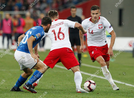 Poland's Jakub Blaszczykowski, center, challenges for the ball with Italy's Alessandro Florenzi during the UEFA Nations League soccer match between Poland and Italy at the Silesian Stadium Chorzow, Poland