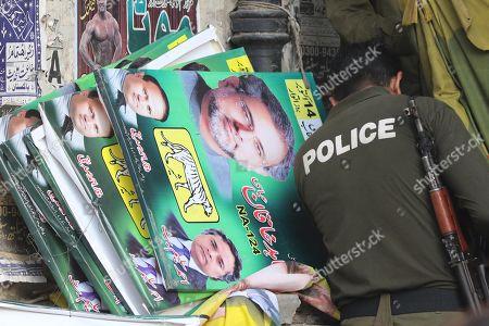 A police officer stands guard beside electoral posters of Shahid Khaqan Abbasi, former Prime Minister outside a polling station during by-elections in Lahore, Pakistan, 14 October 2018. Over 100 candidates are vying for 35 national and provincial assembly seats, which were vacant after the general elections, according to the Election Commission of Pakistan (ECP).