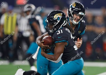 Stock Photo of Jacksonville Jaguars running back Jamaal Charles (31) takes the handoff from quarterback Blake Bortles, right, in the second half of an NFL football game against the Dallas Cowboys in Arlington, Texas