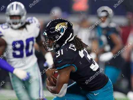 Jacksonville Jaguars running back Jamaal Charles (31) carries past Dallas Cowboys defensive end Demarcus Lawrence (90) in the second half of an NFL football game in Arlington, Texas