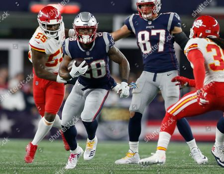 New England Patriots running back James White (28) runs from Kansas City Chiefs linebacker Dee Ford (55) during the second half of an NFL football game, in Foxborough, Mass