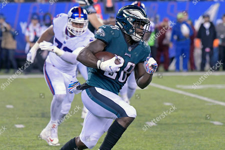 Philadelphia Eagles running back Wendell Smallwood (28) is pursued by New York Giants defensive end Kerry Wynn (72) during the first half of an NFL football game, in East Rutherford, N.J