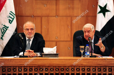 """In this photo released by the Syrian official news agency SANA, shows Syrian Foreign Minister Walid al-Moallem, right, speaks during a press conference with his Iraqi counterpart Ibrahim al-Jaafari, in Damascus, Syria, . Al-Jaafari said Syria should not be isolated from its Arab neighbors, and lauded Damascus for staying """"strong"""" and united in the face of many adversities"""