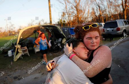 Stock Image of Aurora Bilbro, Ashley Bryant. Aurora Bilbro, left, embraces her childhood friend Ashley Bryant, both 18, in front of the tents they set up for neighbors to sleep in as their homes were damaged from Hurricane Michael in Panama City, Fla