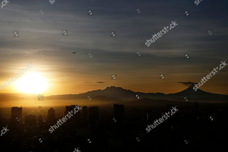 "The sun rises as a plume of ash and steam rise from the Popocatepetl volcano, right, as seen from the in Mexico City, . Geophysicists have noticed an increase in activity at the volcano that sits 45 miles (72 kilometers) southeast of the capital since a 7.1-magnitude earthquake rocked central Mexico in September 2017. The volcano known as ""Don Goyo"" has been active since 1994"