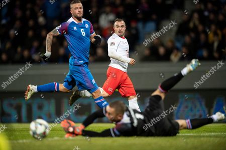 Iceland's Ragnar Sigurdsson (L) and Switzerland's Xherdan Shaqiri (C) in action during the UEFA Nations League soccer match between Iceland and Switzerland at the Laugardalsvoellur stadium in Reykjavik, Iceland, 15 October 2018.