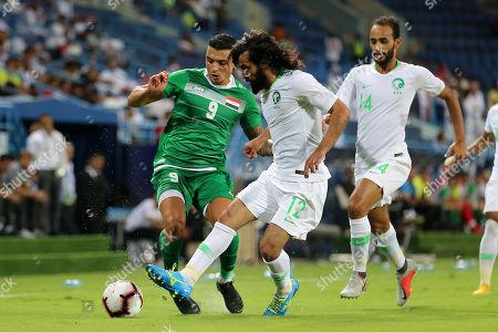 Saudi Arabia's Hussein Abdul-Ghani (C) in action against Iraq's Ahmed Yassin (L) chased by Saudui Arabia's Abdullah Otayf (R) during the friendly international soccer match between Saudi Arabia and Iraq, in Riyadh, Saudi Arabia, 15 October 2018.