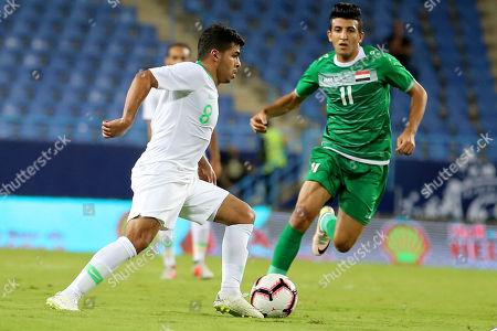 Saudi Arabia's Yahya Al-Shehri (L) in action against Iraq's Amjad Attwan (R)  during the friendly international soccer match between Saudi Arabia and Iraq, in Riyadh, Saudi Arabia, on 15 October 2018.