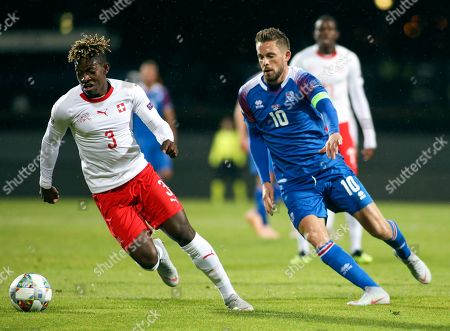 Switzerland's Francois Moubandje, left, is challenged by Iceland's Gylfi Sigurdsson during the UEFA Nations League soccer match between Iceland and Switzerland at Laugardalsvollur stadium in Reykjavik, Iceland
