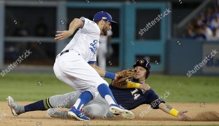 Los Angeles Dodgers' Chris Taylor tags out Milwaukee Brewers' Hernan Perez as he is caught stealing second during the ninth inning of Game 3 of the National League Championship Series baseball game, in Los Angeles