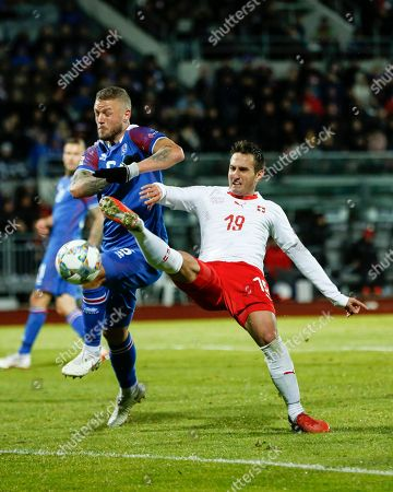 Iceland's Ragnar Sigurdsson (L) battles against Switzerland's Mario Gavranovic (R) during the UEFA Nations League soccer match between Iceland and Switzerland at the Laugardalsvoellur stadium in Reykjavik, Iceland, 15 October 2018.