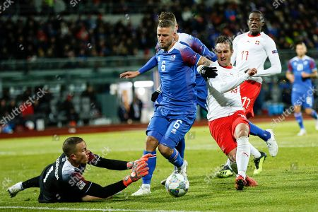 Iceland's goalkeeper Hannes Halldorsson (L) reaches for the ball from Icellands Ragnar Sigurdsson (2-L) and Switzerland's  Mario Gavranovic (R) during the UEFA Nations League soccer match between Iceland and Switzerland at the Laugardalsvoellur stadium in Reykjavik, Iceland, 15 October 2018.