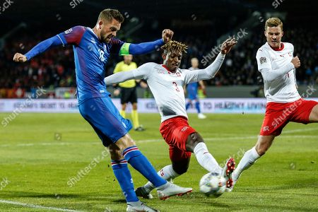 Iceland's Gylfi Sigurdsson (L) in action against Switzerland's Francois Moubandje (C) during the UEFA Nations League soccer match between Iceland and Switzerland at the Laugardalsvoellur stadium in Reykjavik, Iceland, 15 October 2018.