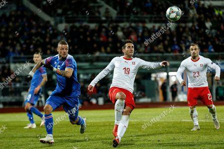 Iceland's Ragnar Sigurdsson (L) in action against Switzerland's Mario Gavranovic (C) and Xheridan Shaqiri (L) in during the UEFA Nations League soccer match between Iceland and Switzerland at the Laugardalsvoellur stadium in Reykjavik, Iceland, 15 October 2018.