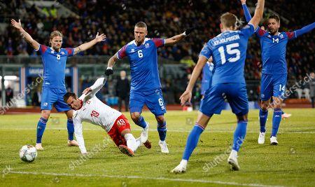 Iceland Switzerland Nations League Soccer. Switzerland's Mario Gacranovic (19), second to left, is challenged by Iceland's, from left, Birkir Bjarnason (8), Ragnar Sigurdsson (6), Holmar Eyjolfsson (15) and Kari Arnason (14) during the UEFA Nations League soccer match between Iceland and Switzerland at Laugardalsvollur stadium in Reykjavik, Iceland