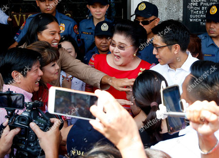 Imee Marcos, Imelda Marcos, Ferdinand Marcos Jr. Former First Lady and now Congresswoman Imelda Marcos, center, reacts as her daughter Governor Imee Marcos, second from left, and son Ferdinand Marcos Jr., left, arrive at the Commission on Elections to lend support to Imee in filing her Certificate of Candidacy or COC for a Senate seat in the May 2019 midterm elections in Manila, Philippines. Close to a hundred senatorial hopefuls have so far filed their certificates of candidacy for the 13 senatorial seats available for next year's elections