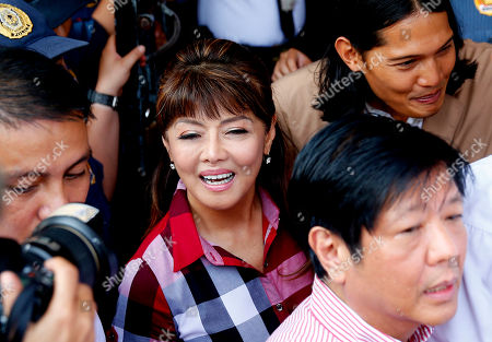 """Imee Marcos, Ferdinand Marcos Jr., Borgy Marcos. Governor Imee Marcos, center, the daughter of the late strongman Ferdinand Marcos, makes her way through a crowd of supporters as she arrives at the Commission on Elections to file her Certificate of Candidacy or COC for a Senate seat in the May 2019 midterm elections, in Manila, Philippines. Close to a hundred senatorial hopefuls have so far filed their certificates of candidacy for the 13 senatorial seats available for next year's elections. At bottom right is her brother, former Senator Ferdinand """"Bongbong"""" Marcos Jr., and top right is Imee's son Borgy"""