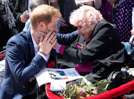 Britain's Prince Harry is embraced by 97-year-old Dafney Dunne during a walk about outside the Opera House in Sydney, Australia,. Prince Harry and his wife Meghan are on a 16-day tour of Australia and the South Pacific