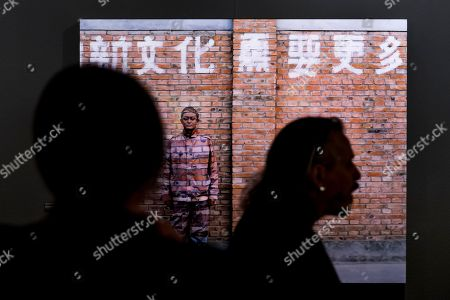 People look at the work of Chinese photographer and artist Liu Bolin (New Culture Needs More..., 'Hiding in the City' 2005) during his new exhibition 'Le Theatre des apparences' at the Musee de l'Elysee in Lausanne, Switzerland, 16 October 2018.