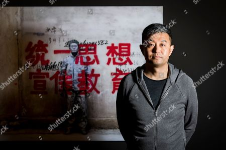Chinese photographer and artist Liu Bolin poses in front of his work (Unify the Thought to Promote Education More, 'Hiding in the City' 2007) during his new exhibition 'Le Theatre des apparences' at the Musee de l'Elysee in Lausanne, Switzerland, 16 October 2018.