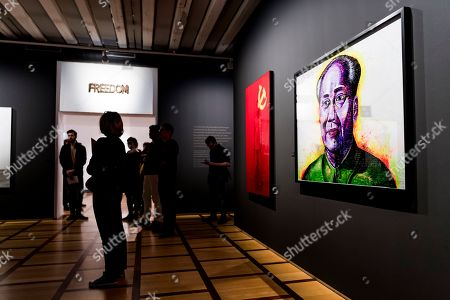 People look at the work of Chinese photographer and artist Liu Bolin (Head Portrait (Mao), 'Hiding in the City' 2012) during his new exhibition 'Le Theatre des apparences' at the Musee de l'Elysee in Lausanne, Switzerland, 16 October 2018.