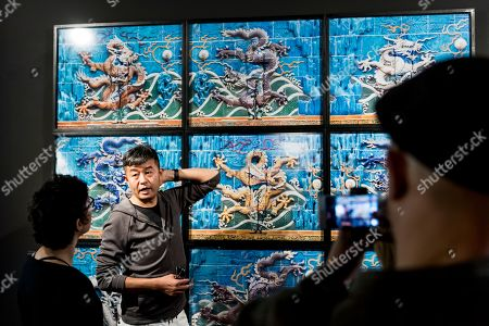 Chinese photographer and artist Liu Bolin speaks in front of his work (Nine-Dragon Screen, 'Hiding in the City' 2010) during his new exhibition 'Le Theatre des apparences' at the Musee de l'Elysee in Lausanne, Switzerland, 16 October 2018.
