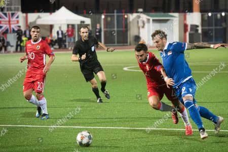 Gibraltar's John Sergeant, 2nd right, and Liechtenstein's Marcel Buchel challenge for the ball during the UEFA Nations League soccer match between Gibraltar and Liechtenstein at the Victoria Stadium in Gibraltar