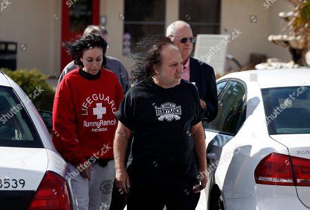 """Ron Jeremy, front right, and Heidi Fleiss, left, walk out of the Love Ranch brothel, in Pahrump, Nev. Dennis Hof, a pimp who gained notoriety for an HBO series about his brothel business, was found dead hours after his 72nd birthday bash, authorities said Tuesday. Hof had said his party would be attended by porn star Jeremy. It wasn't immediately clear Tuesday if Jeremy attended. Hof upended Nevada politics this summer when he ousted an incumbent Republican lawmaker in a primary, celebrating at an election night party with """"Hollywood Madam"""" Fleiss"""
