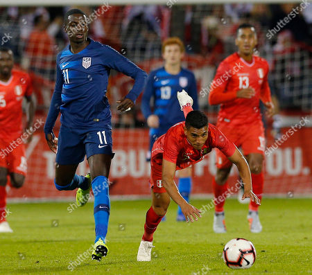 United States midfielder Tim Weah (L) trips Peru midfielder Paolo Hurtado (R) during the first half of the friendly match between the United States and Peru at Pratt and Whitney Field in East Hartford, Connecticut, USA, 16 October 2018.