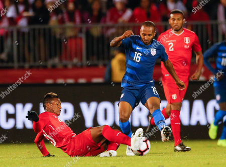 Peru midfielder Pedro Aquino (L) tries to keep the ball from Julian Green (C) of the United States during the second half of the friendly match between the United States and Peru at Pratt and Whitney Field in East Hartford, Connecticut, USA, 16 October 2018.