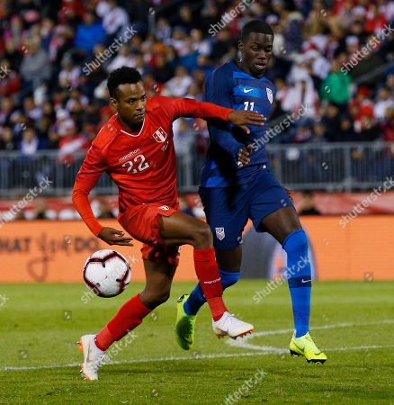 Peru defender Nilson Loyola (L) keeps the ball from United States midfielder Tim Weah (R) during the second half of the friendly match between the United States and Peru at Pratt and Whitney Field in East Hartford, Connecticut, USA, 16 October 2018.