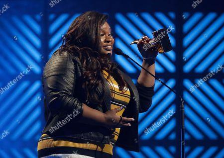 Stock Image of Tasha Cobbs Leonard accepts the Gospel Artist of the Year award during the Dove Awards, in Nashville, Tenn