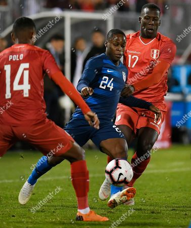 United States' Jonathan Amon (24) splits the defense of Peru's Andy Polo (14) and Luis Advíncula (17) during the first half of an international friendly soccer match in East Hartford, Conn