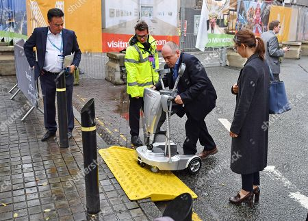 Stock Picture of The Rt Hon Robert Halfon MP (centre) Has Trouble Negotiating A Steep Camber On His Powered Vehicle In The Conference Zone. Conservative Party Conference At Manchester Central Convention Centre Greater Manchester. 1/10/17.