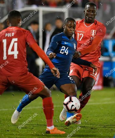 Andy Polo, Jonathan Amon, Luis Advíncula. United States' Jonathan Amon (24) splits the defense of Peru's Andy Polo (14) and Peru's Luis Advíncula (17) during the first half of an international friendly soccer match in East Hartford, Conn