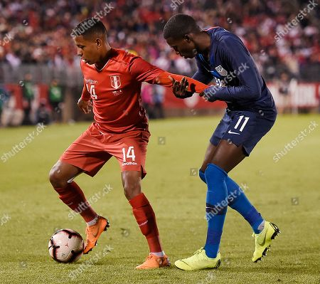 Andy Polo, Tim Weah. United States' Tim Weah (11) holds the arm of Peru's Andy Polo (14) as Polo tries to pull forward during the first half of an international friendly soccer match in East Hartford, Conn