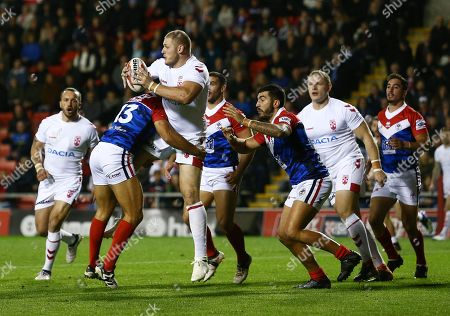 Tom Burgess of England is tackled by Mickael Goudemand of France